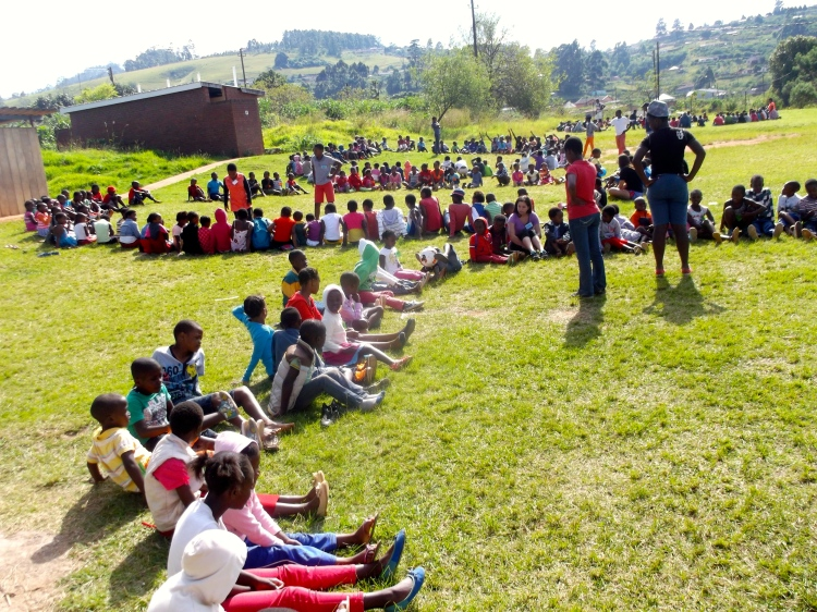 Kids sitting in their four groups to play a ball game